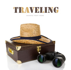Black modern binoculars with suitcase and straw hat isolated