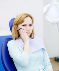 woman at the dentist complains of toothache. Looking at camera.