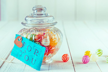 Candy jar filled with candies with a blue tag