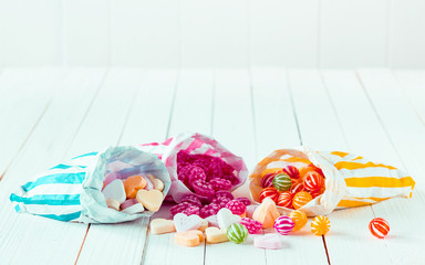 Assortment of candies in three bags over a table