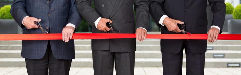 Einweihung - Geschäftsmänner durchschneiden rotes Band