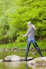 woman fishing in Sazava river, Czech Republic