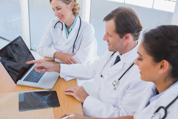 Smiling doctor showing laptop screen to colleagues
