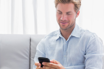 Man using his phone on a couch