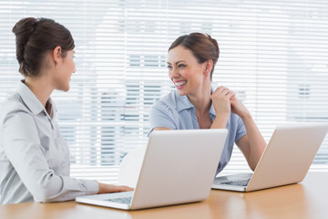 Businesswoman laughing together at desk