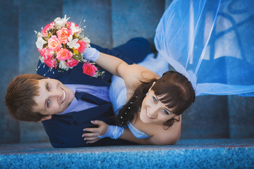 portret of happy newlyweds on stairs. top view