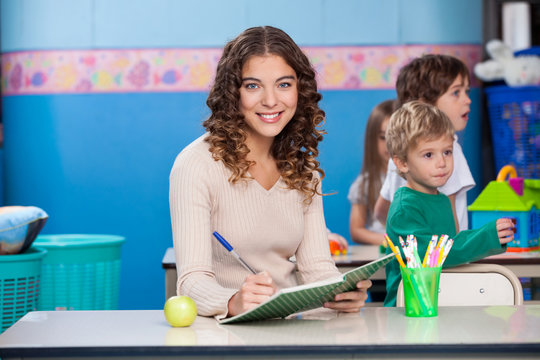 Teacher Writing In Book With Children Playing In Background