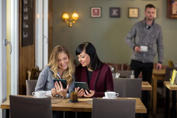 Female Friends Using Digital Tablets At Cafe