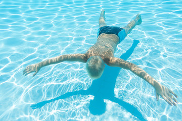 boy swims under water face down in a pool