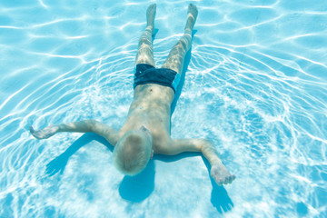 boy swims under water face up in a pool