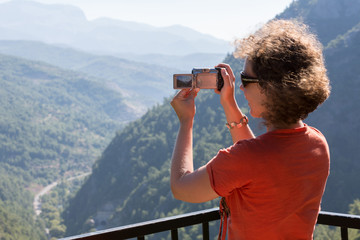 girl make photo on camera beautiful view of mountains