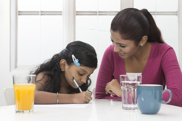 Indian mum helping child with homework