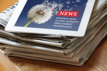 Digital tablet internet news on paper newspaper