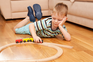 Little child playing with wooden railway