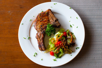 Pork chop with salad on table top view
