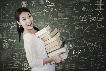 Attractive female bring pile of books in class