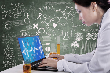 Beautiful scientist working with laptop at workplace
