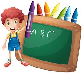 A little boy holding a big violet crayon near the blackboard