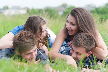Four happy teenage friends lying together on green grass