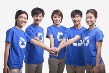 Five young people in recycling t-shirts with hands together, studio shot