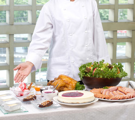 Female chef showing a lot of cooked food and bakery
