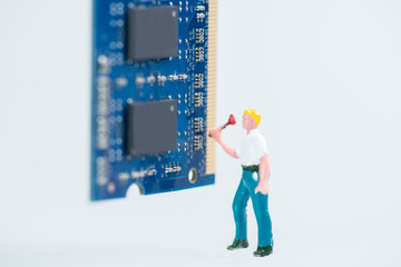 Miniature workman working on the computer RAM close up
