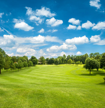 green golf field and blue cloudy sky