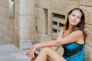 Young woman sitting on footsteps in old town