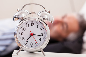Alarm Clock In Front Of Man Sleeping