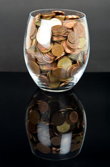 Coins in glass over black