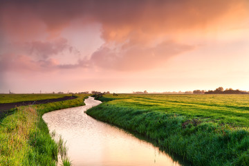 Wall Mural - dramatic sunrise over canal in farmland