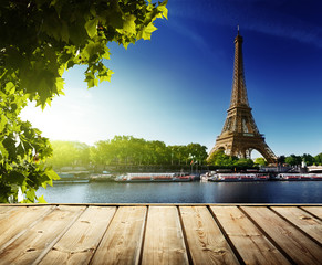 Garden Poster Paris background with wooden deck table and Eiffel tower in Paris