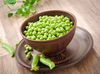 Green peas in a ceramic bowl on old wooden background