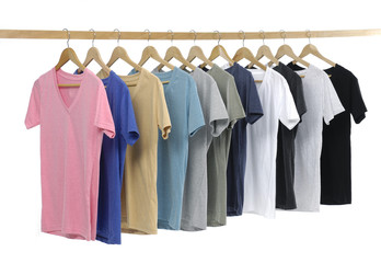 man clothes of different colors t-shirt on wooden hangers