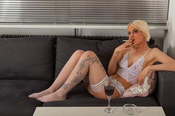 Junge Frau in weißen Dessous auf dem Sofa