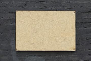 Cork board on a grey brick wall
