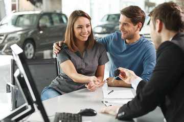 Now her dream comes true. Car salesman giving the key of the new
