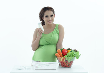 Pregnant woman with bowl of salad.
