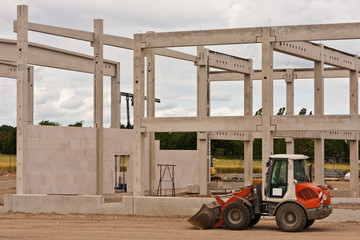 Ein Radlader vor dem Rohbau einer Betonkonstruktion