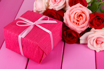 Beautiful bouquet of roses with gift on table close-up