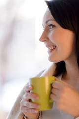 Woman drinking coffee. Beautiful middle-aged woman standing in f