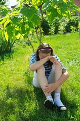 Fototapeta płacząca dziewczynka pod drzewem obraz