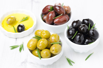 three kinds of olives in bowls, fresh rosemary and olive oil