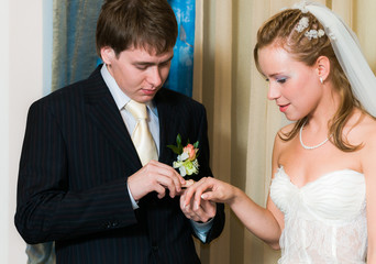 Young wedding couple putting the ring