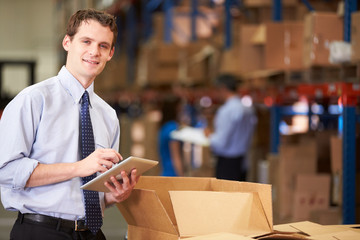 Manager In Warehouse Checking Boxes Using Digital Tablet