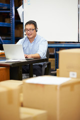 Worker In Warehouse Wearing Headset And Using Laptop