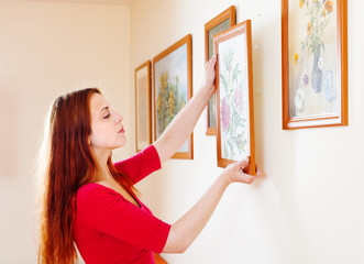woman in red hanging the art pictures