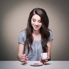 Young woman drinking a coffee. Grey studio background.