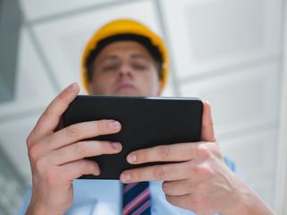 engineer in a helmet with a digital tablet