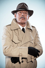 Retro detective man with mustache and hat. Wearing raincoat. Stu